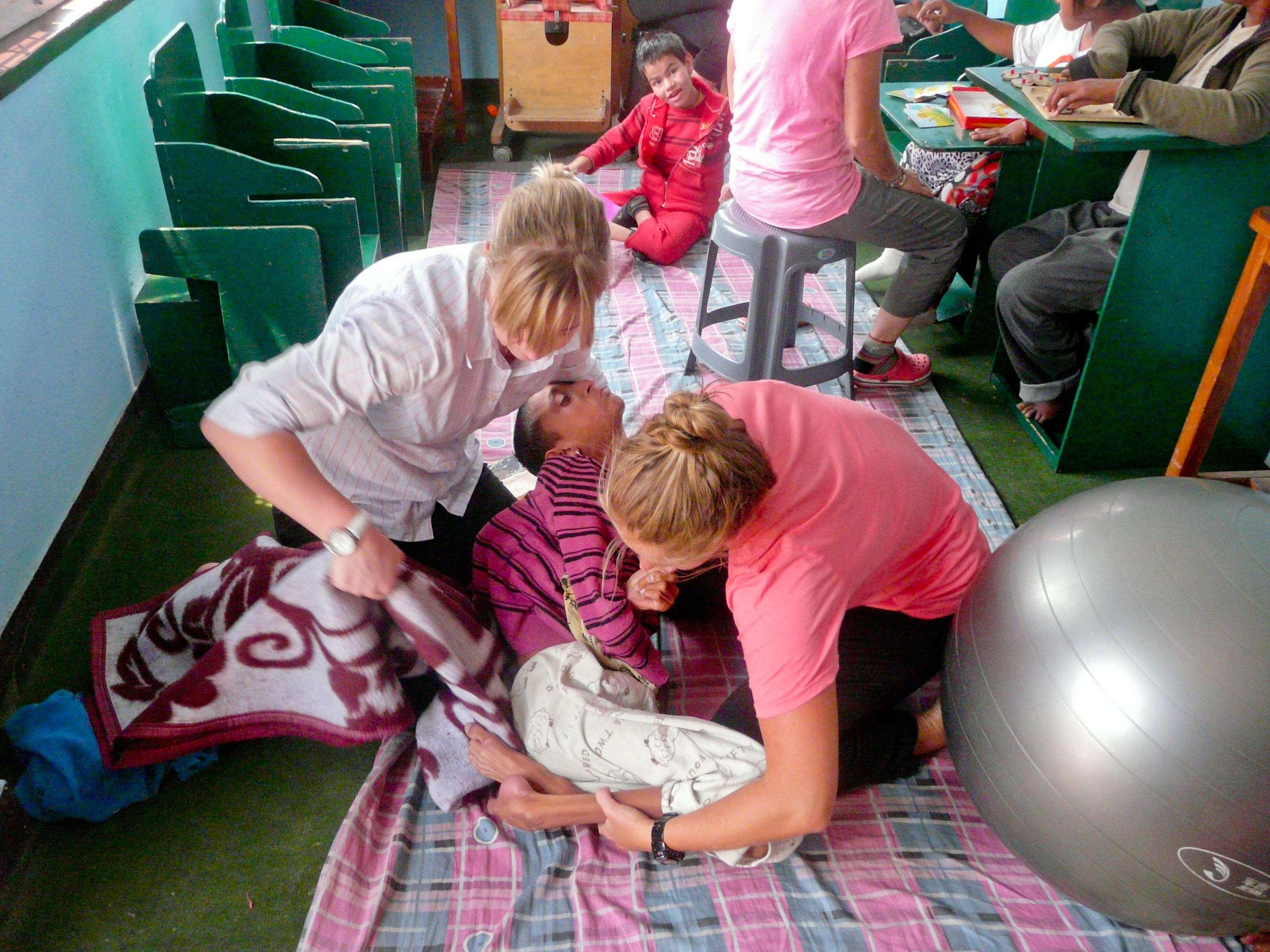 Two female interns are pictured helping a local disable child stretch and exercise his legs whilst on a physiotherapy internship in Nepal with Projects Abroad.